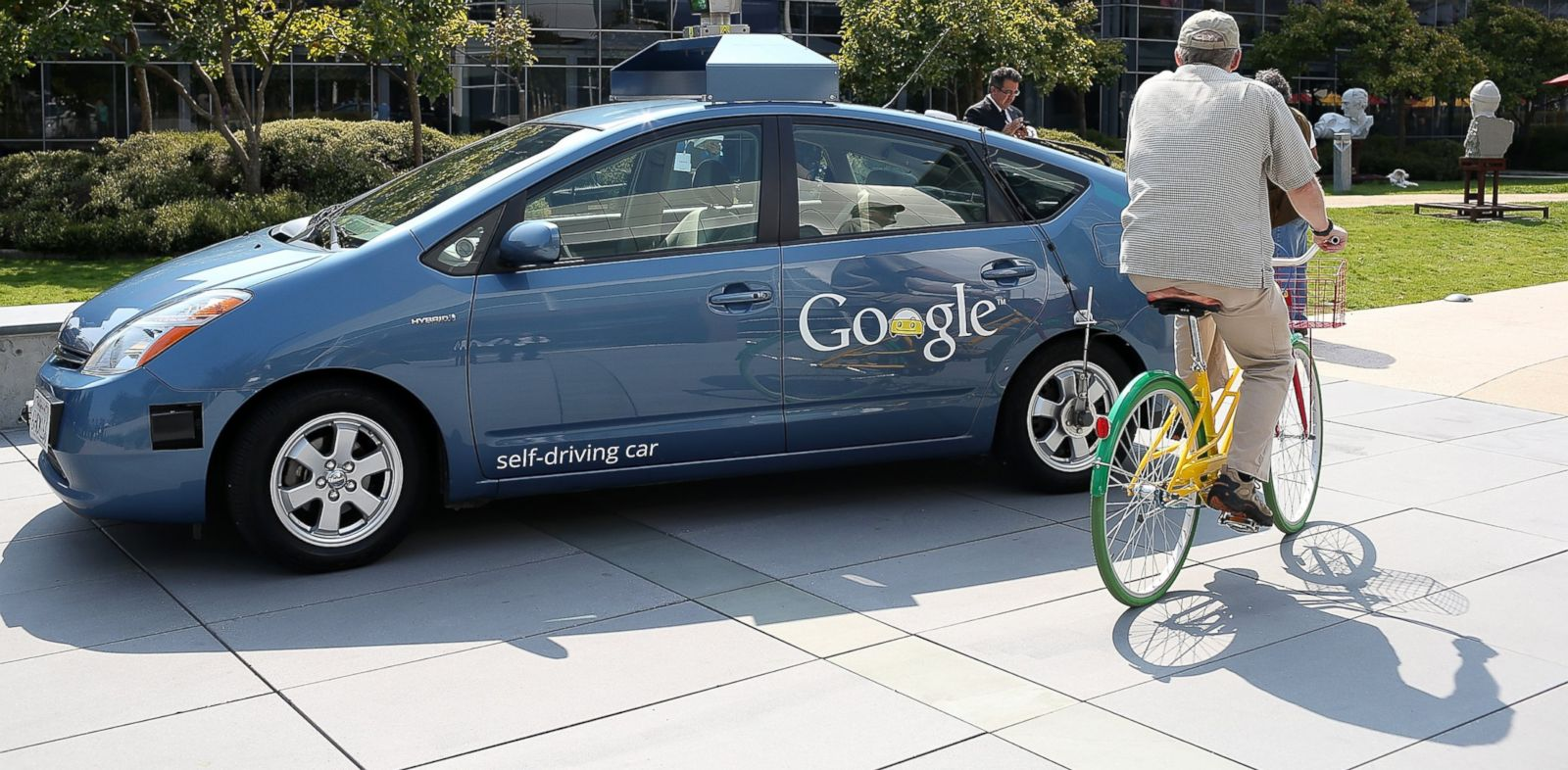 PHOTO: A bicyclist rides by a Google self-driving car at the Google headquarters, Sept. 25, 2012, in Mountain View, California.
