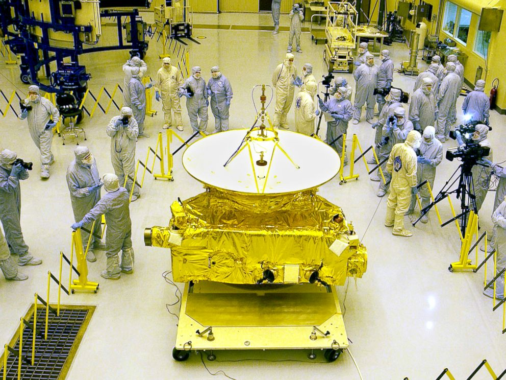 PHOTO: Members of the media garbed in protective uniforms view NASAs New Horizons spacecraft on Nov. 4, 2005 at Kennedy Space Center in Florida.