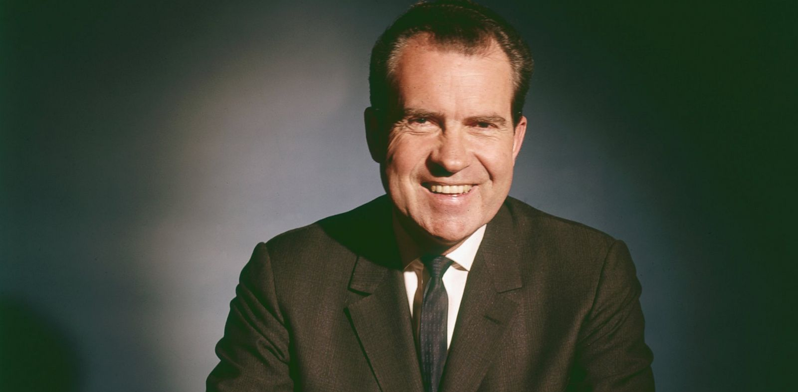 PHOTO: Portrait of American politician and President Richard Nixon as he smiles and sits at a table, 1960s.