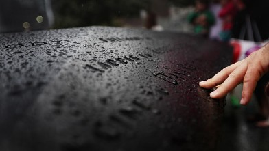 PHOTO: Visitors view names of the deceased at the National September 11 Memorial in the rain on the fourth day it was open to the public on Sept. 15, 2011 in New York City.