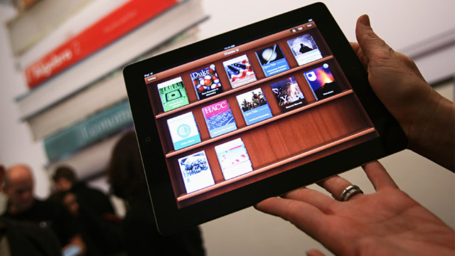 PHOTO: A woman holds up an iPad, with iBooks textbooks shown in the iTunes U app, after a news conference introducing a digital textbook service, Jan. 19, 2012, in New York.