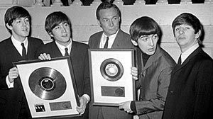 PHOTO Alan Livingston (center), president of Capitol Records, and the Beatles display gold records presented to the quartet during a ceremony