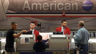 PHOTO: American Airlines employees help travelers at the ticket counter in the Miami International Airport on Feb. 12, 2013 in Miami.