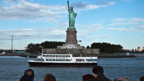 PHOTO: A group of tourists passes near the Statue of Liberty as they enjoy a ride in New York harbor