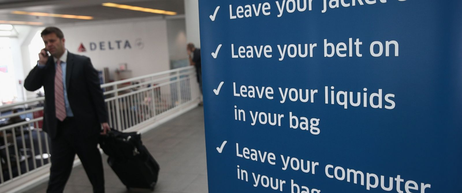 PHOTO: A traveler walks past a newly-opened TSA Pre-check application center at LaGuardia Airport