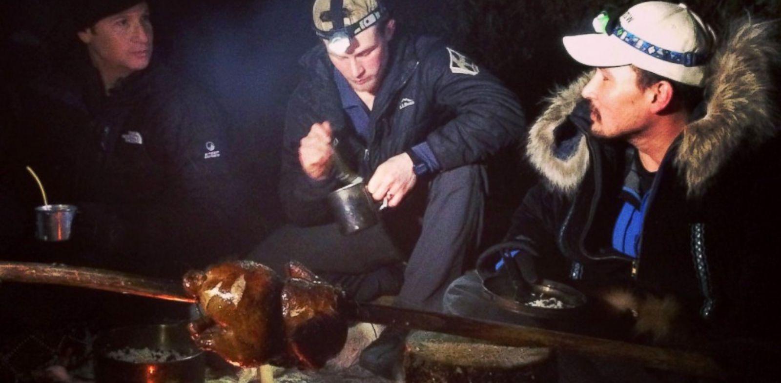 PHOTO: ABCs Neal Karlinsky, left, Dallas Seavey, center, and Eddie Ahyakak, right, sit around a campfire in the Alaskan wilderness.