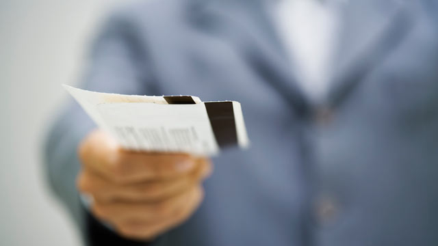 PHOTO: Airplane ticket counter personnel holding out boarding passes.