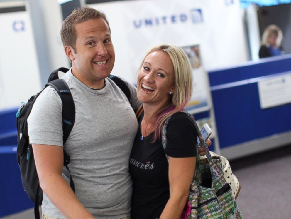 PHOTO: Sarah Lynn and David Olson are all smiles when they arrive at the airport en route to meeting their daughter, Tilly.
