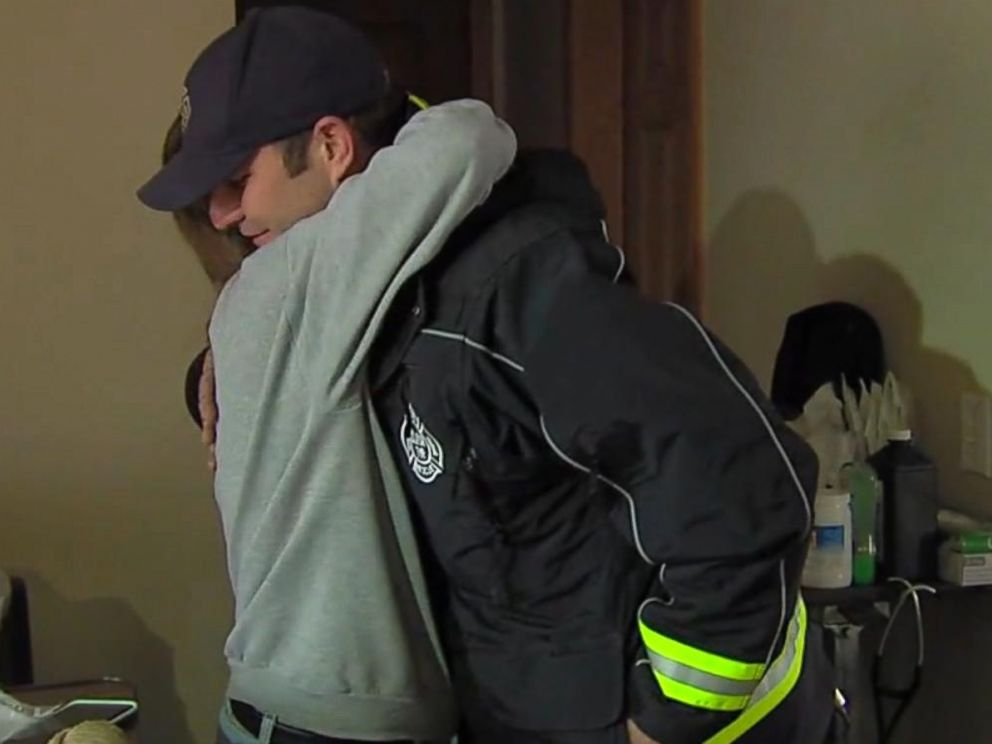 PHOTO: Firefighter Ryan McCuen is hugged by a member of the Stone family. McCuen paid their electric bill after he responded to a call and found that their 18 year old son, Troy, was not able to use his ventilator because power had been cut off.