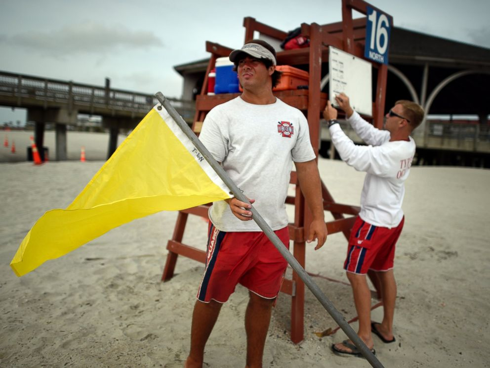 PHOTO: Tybee Island Ocean Rescue Senior Lifeguard Todd Horne, right, and Mark Eichenlaub, left, prepare to hang a yellow flag that warns swimmers of strong rip currents from Hurricane Arthur along the beach on Tybee Island, Ga., July 3, 2014.