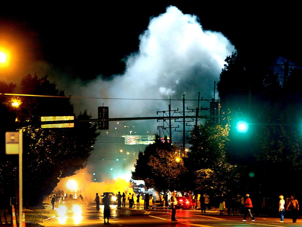 PHOTO: Police officers work their way north on West Florissant Avenue in Ferguson, Mo., clearing the road with the use of tear gas and smoke bombs, Aug. 13, 2014.
