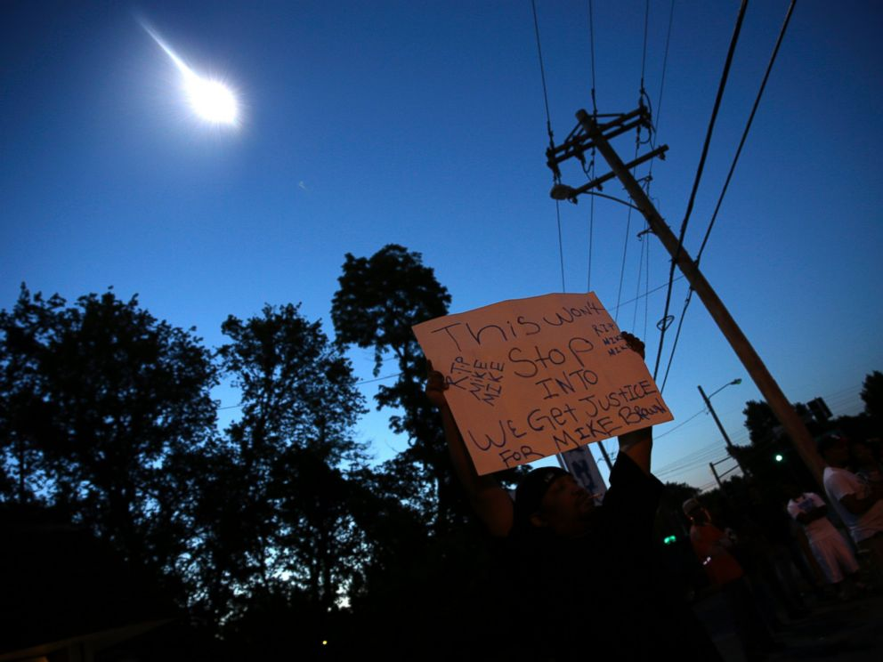 PHOTO: A protester holds up a sign as a police helicopter circles overhead, Aug. 13, 2014, in Ferguson, Mo.
