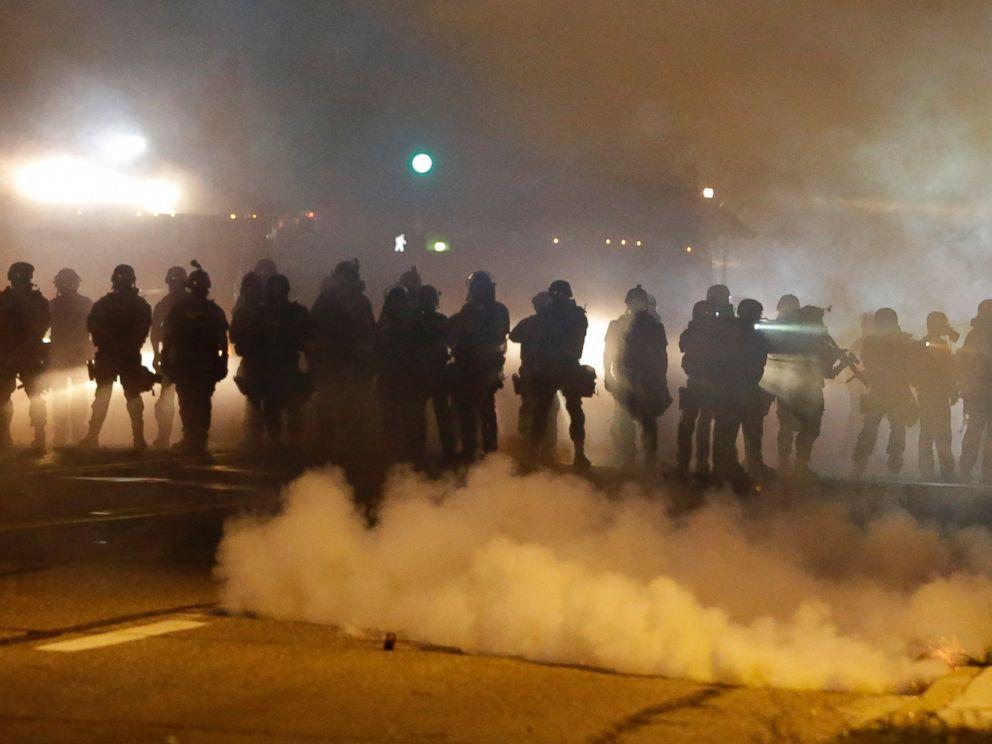 PHOTO: Police advance through smoke, Aug. 13, 2014, in Ferguson, Mo.