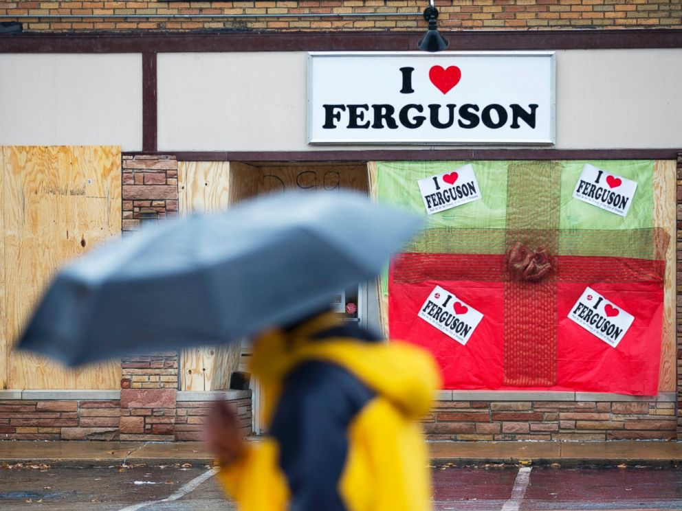 PHOTO: A pedestrian passes a boarded up storefront selling I Love Ferguson paraphernalia, Nov. 23, 2014, in Ferguson, Mo.