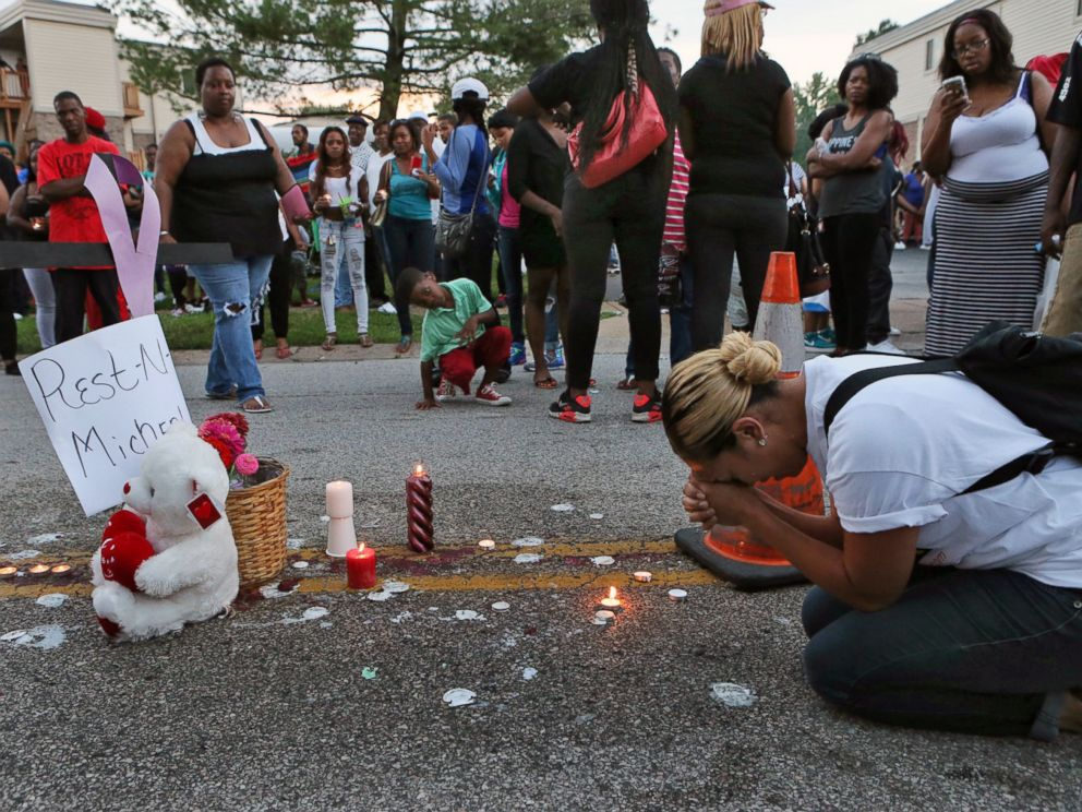 PHOTO: Meghan ODonnell, 29, from St. Louis, prays at the spot where Michael Brown was killed, Aug. 10, 2014, in Ferguson, Mo.