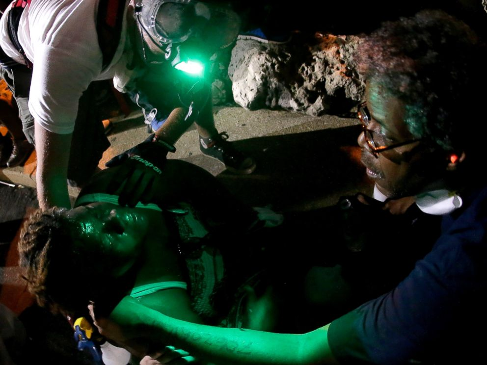 PHOTO: People help a woman sprayed with chemicals after police attempted to disperse a protest in Ferguson, Mo., Aug. 20, 2014.