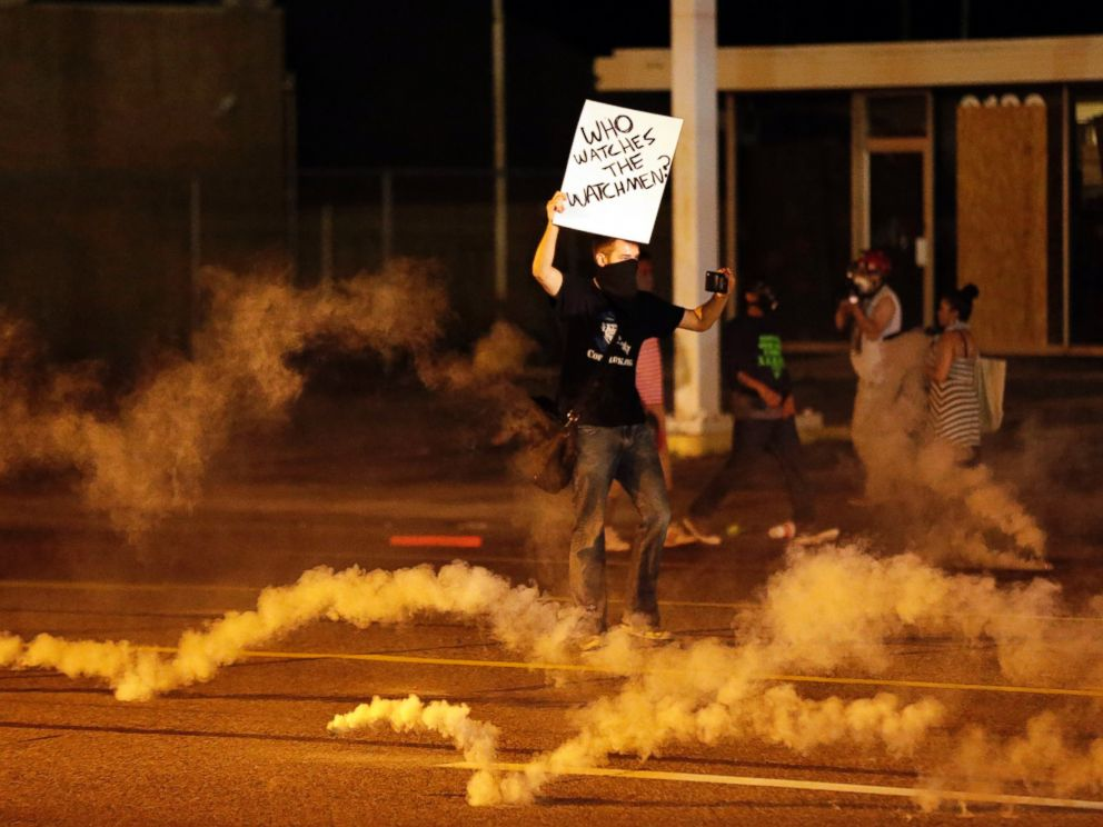 PHOTO: A protester stands in the street after police fired tear gas to disperse a crowd in Ferguson, Mo., Aug. 17, 2014.