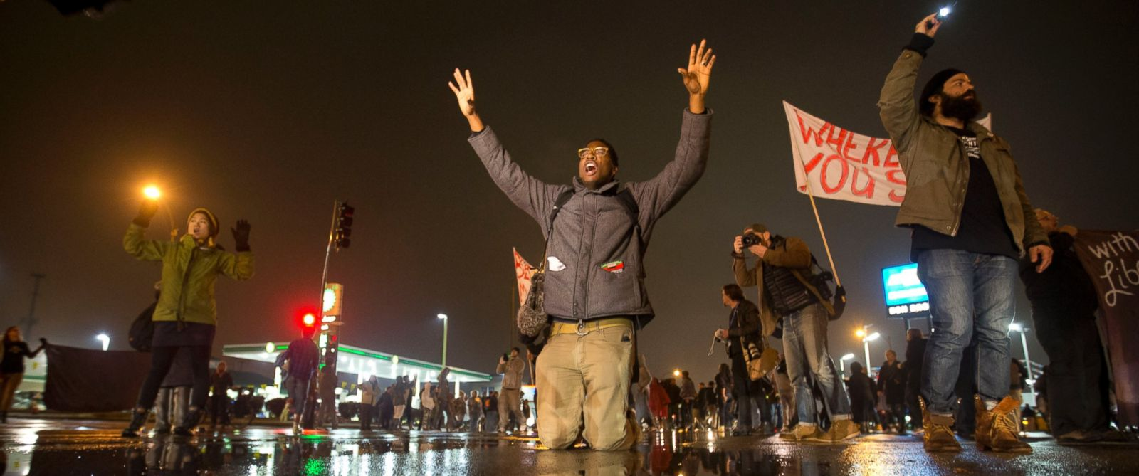 PHOTO: Anthony Grimes kneels on a rain-soaked street as he blocks traffic with other protesters, Nov. 23, 2014, in St. Louis.
