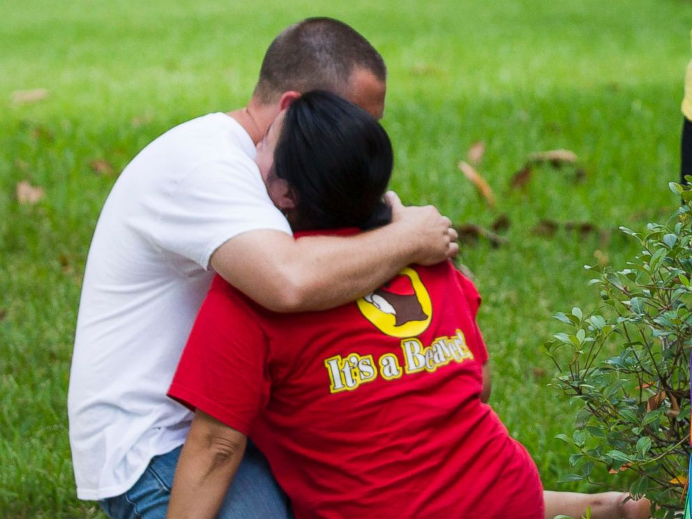 PHOTO: Neighbors embrace each other following a shooting, July 9, 2014, in Spring, Texas.