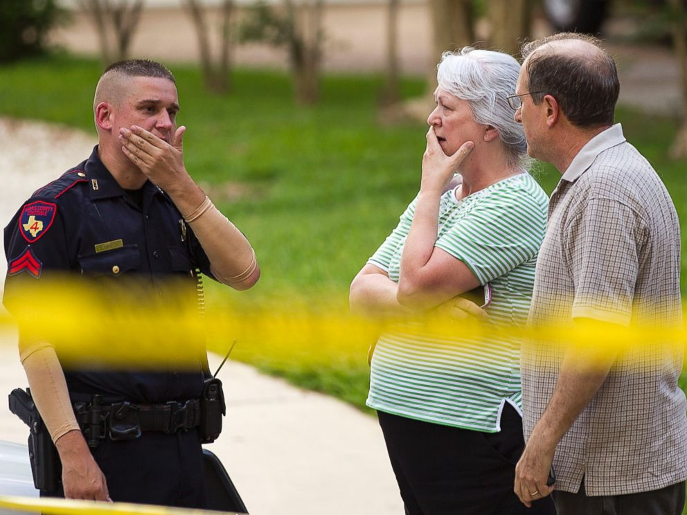 PHOTO: People stand with a law enforcement officer near the scene of a shooting, July 9, 2014, in Spring, Texas.