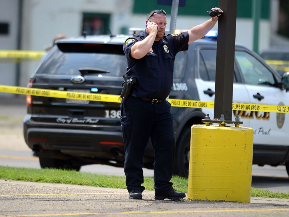 PHOTO: A law enforcement officer speaks on a phone near the site of a shooting in West St. Paul, Minn., July 30, 2014.