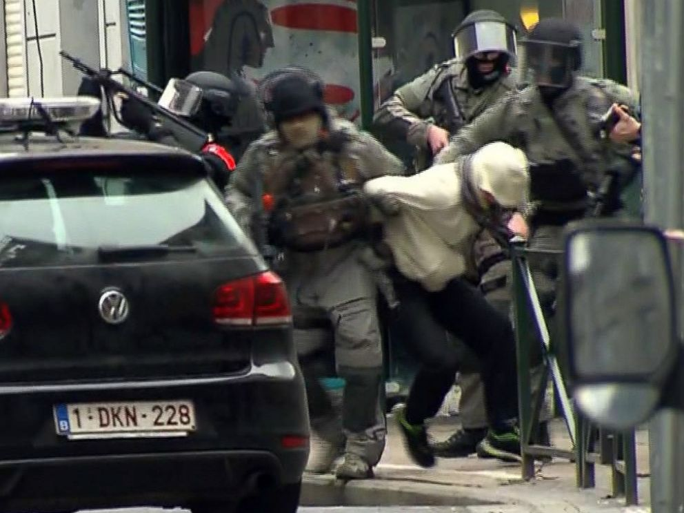 PHOTO: Armed police officers carry a suspect to a police vehicle during a raid in the Molenbeek neighborhood of Brussels, Belgium, March 18, 2016.