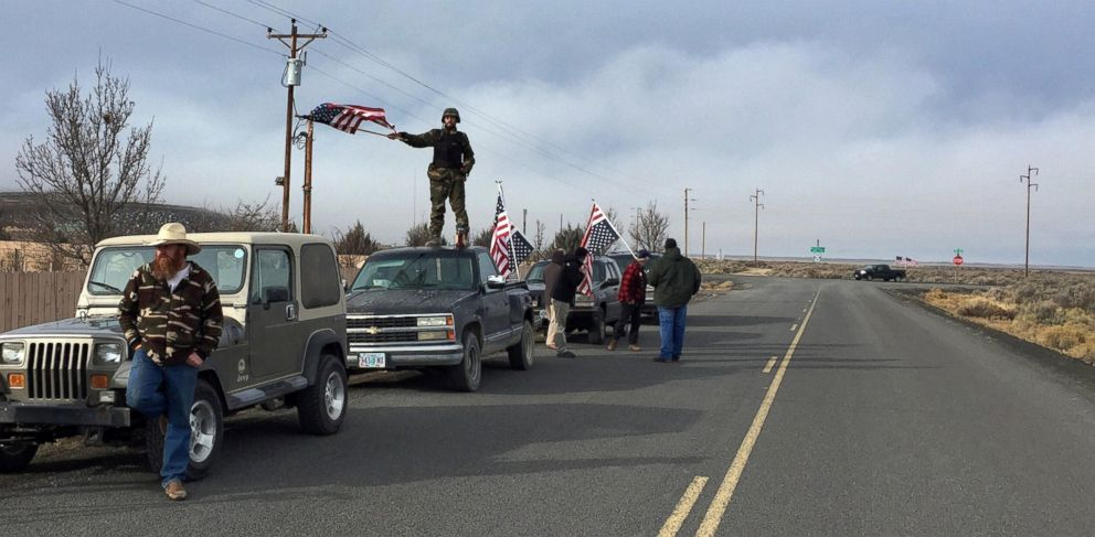 PHOTO: People wave American flags near the Malheur National Wildlife Refuge, Feb. 11, 2016, near Burns, Ore.