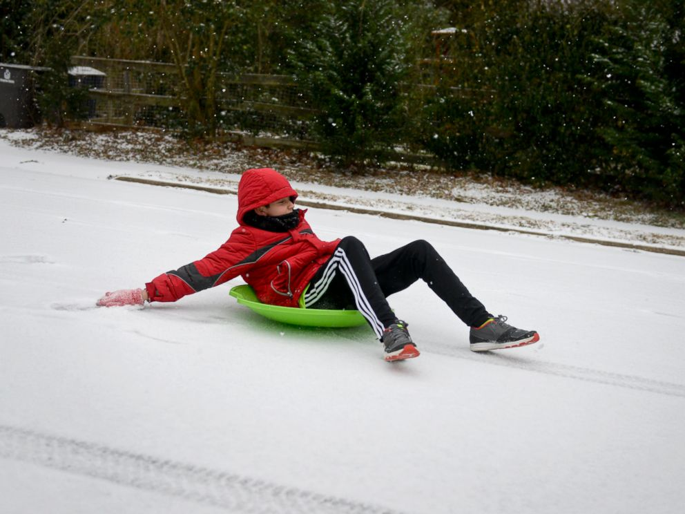 PHOTO: Pablo Hortal, 11, sleds down a street in Winston-Salem, N.C. as snow falls, Feb. 16, 2015.