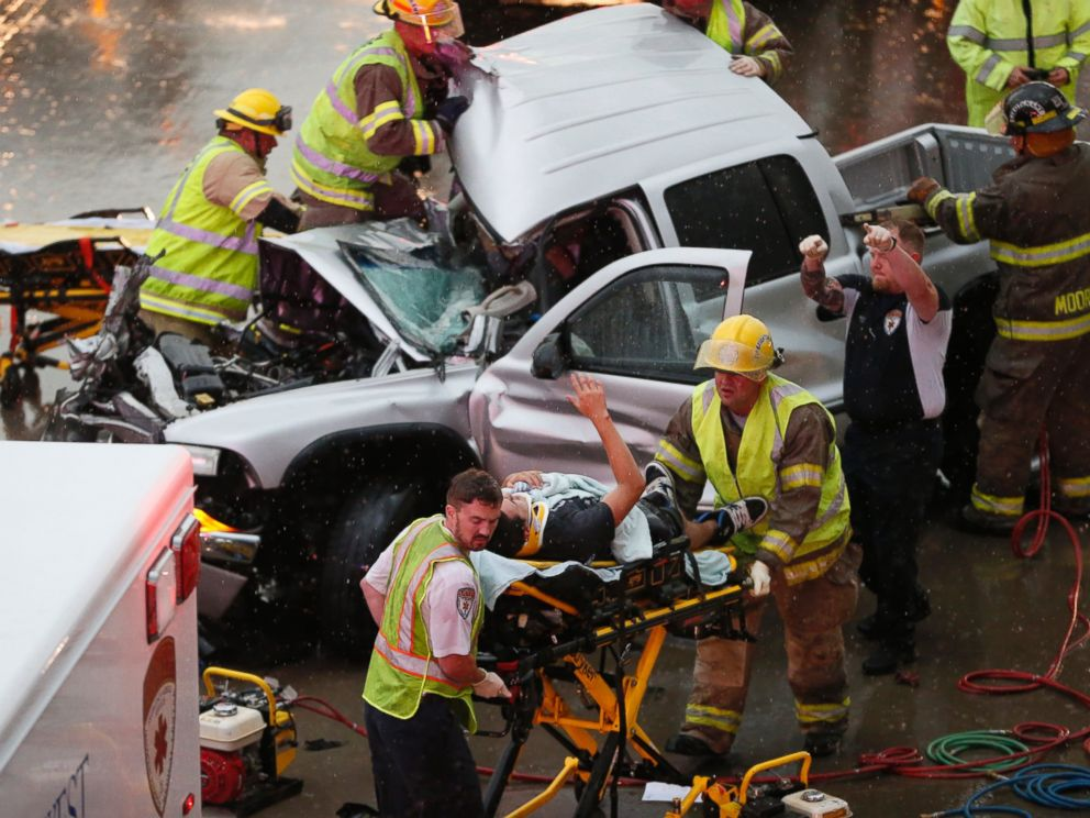 PHOTO: The driver of a truck which crashed during severe weather on Interstate 35 gestures to his rescuers after being cut from the truck in Moore, Okla., May 6, 2015.