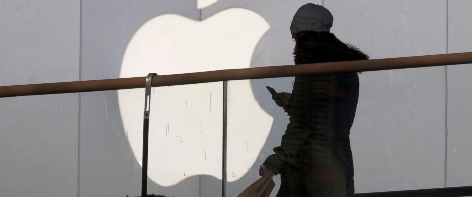 PHOTO: A woman walks past Apples logo.