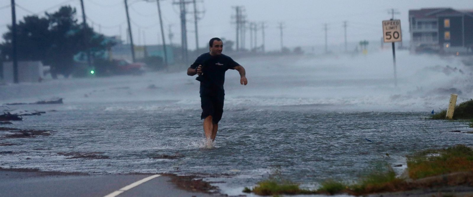 PHOTO: A man crosses flooded Highway 64 as Hurricane Arthur passes through Nags Head, N.C., July 4, 2014.