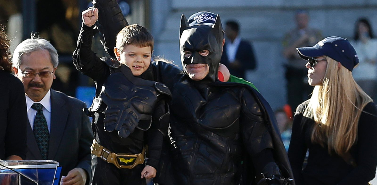 PHOTO: Miles Scott, dressed as Batkid, second from left, raises his arm next to Batman at a rally outside of City Hall with Mayor Ed Lee, left, and his mother Natalie Scott in San Francisco, Nov. 15, 2013.