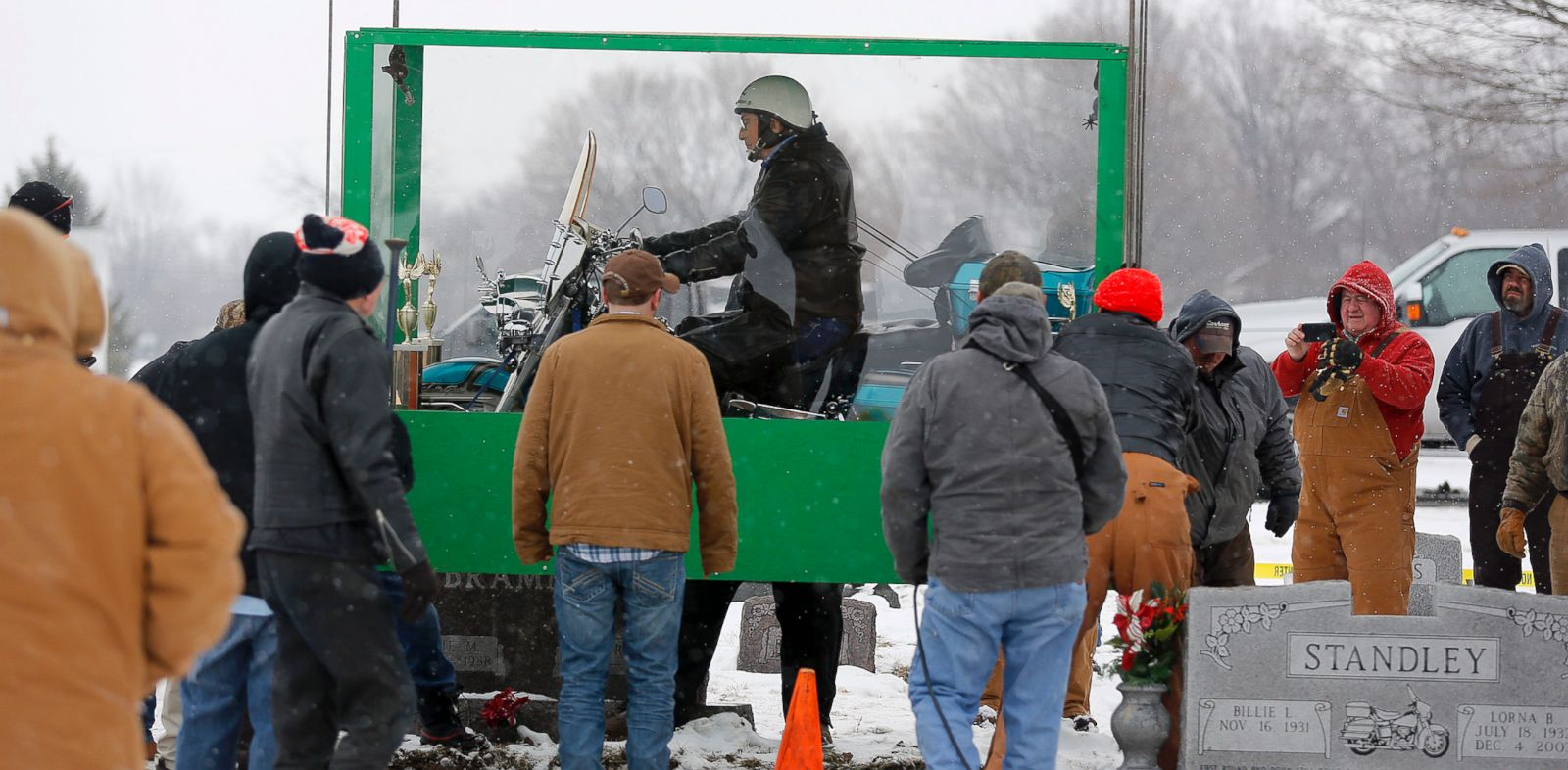 PHOTO: The body of Bill Standley, secured to his 1967 Harley Davidson, rests inside a plexiglass box before being lowered into the ground at the cemetery in Mutual, Ohio on Friday, Jan. 31, 2014.