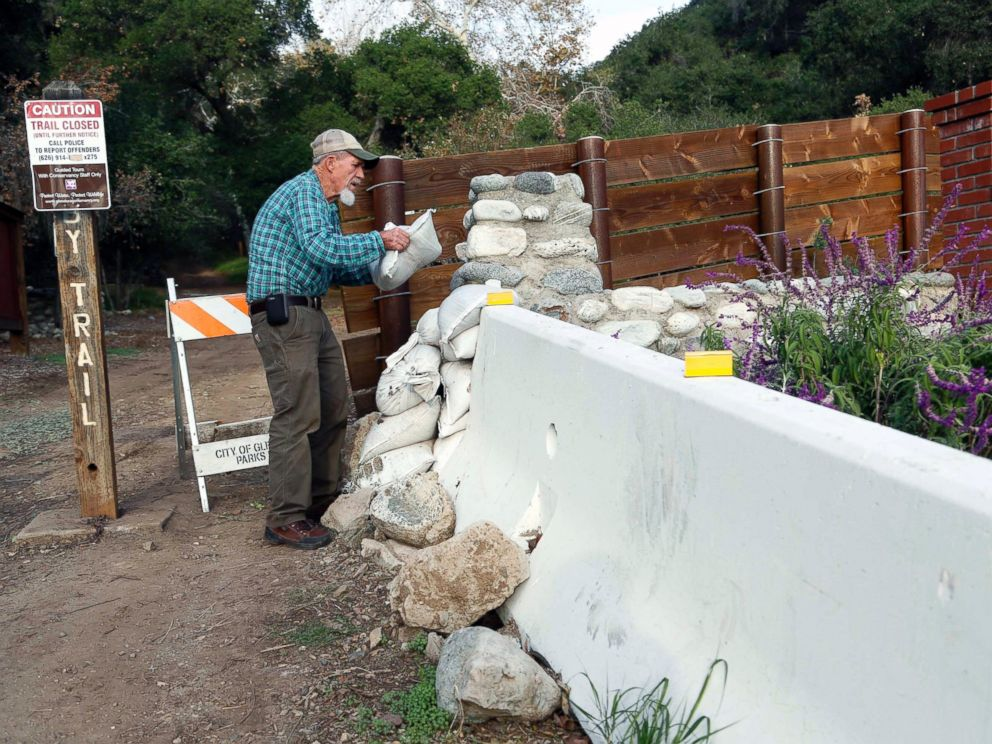 PHOTO: Jerry Croissant, 77, places sandbags to protect his home from mudslides outside his home in Gelndra, Calif., below mountains burned over in wildfires, Dec. 10, 2014.