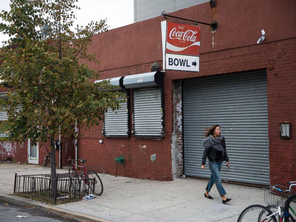 PHOTO: A pedestrian walks past The Gutter bowling alley in the Williamsburg neighborhood of New York on Friday, Oct. 24, 2014.