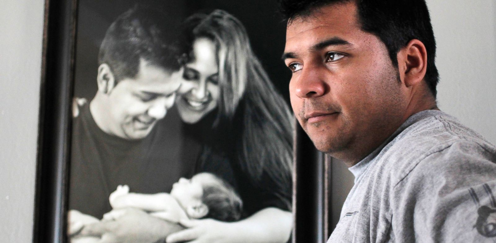 PHOTO: Erick Munoz stands with an undated photograph of himself, left, with wife Marlise and their son Mateo, in Haltom City, Texas.