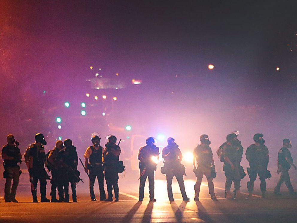 PHOTO: Police officers work their way north on West Florissant Avenue in Ferguson, Mo., clearing the road of people, Aug. 13, 2014.