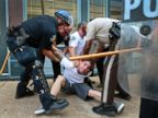 PHOTO: Police officers arrest a man who refused to leave when police in riot gear cleared the area of S. Florissant Road and Church Street in downtown Ferguson, Mo., Aug. 11, 2014.