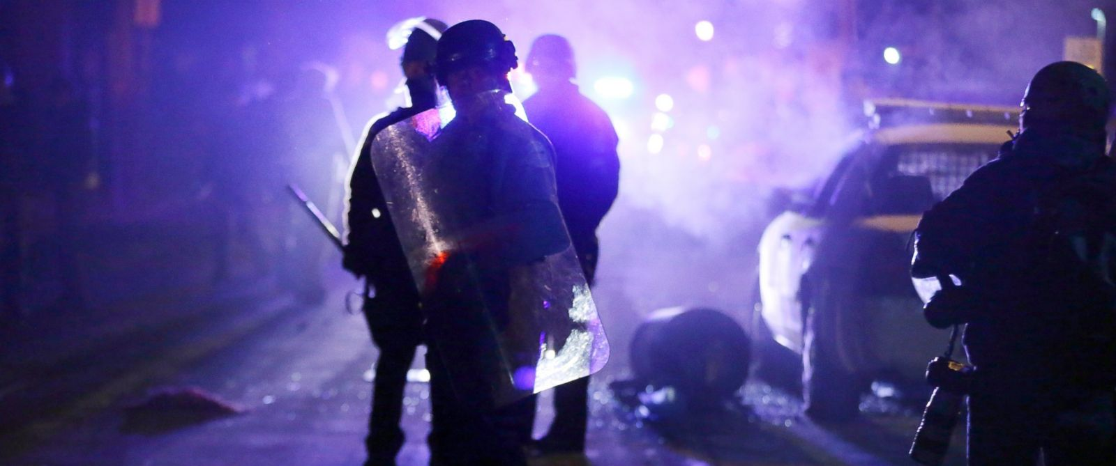 PHOTO: Police officers watch protesters as smoke fills the streets in Ferguson, Mo., Nov. 25, 2014.