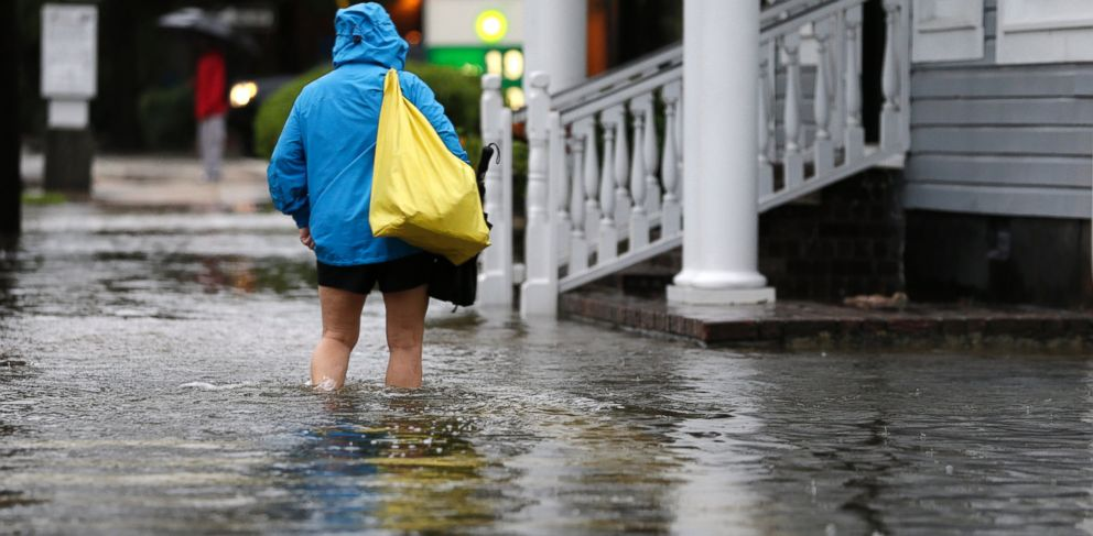 PHOTO: A woman walks down a flooded sidewalk toward an open convenience store in Charleston, S.C., Oct. 4, 2015.