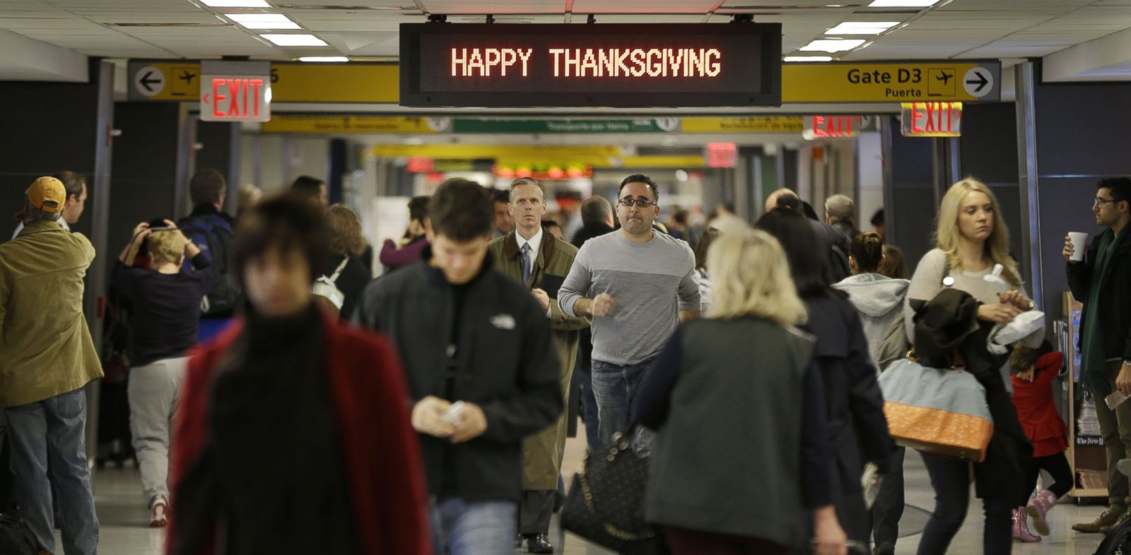 "PHOTO: Travelers walk under a sign reading ""Happy Thanksgiving"" at LaGuardia Airport in New York, Nov. 26, 2013."