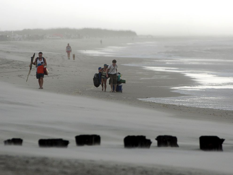 PHOTO: Clouds and rains move in as beachgoers leave Freeman Park at the north end of Carolina Beach, N.C., July 3, 2014.