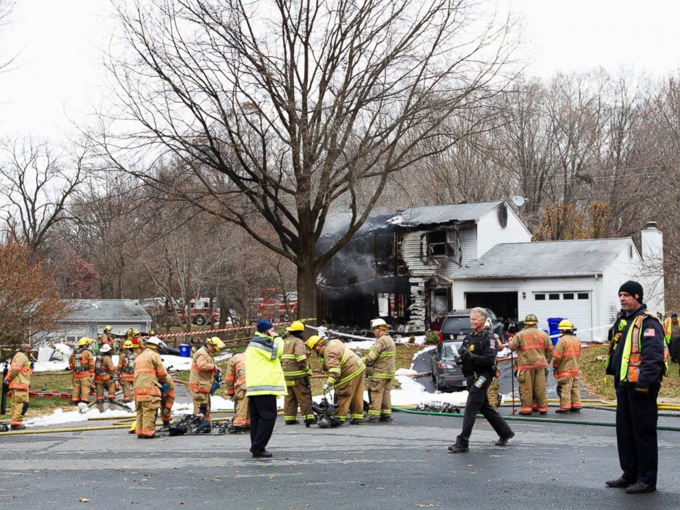PHOTO: Montgomery County, Md. firefighters stand outside a house where a small plane crashed in Gaithersburg, Md., Dec. 8, 2014.