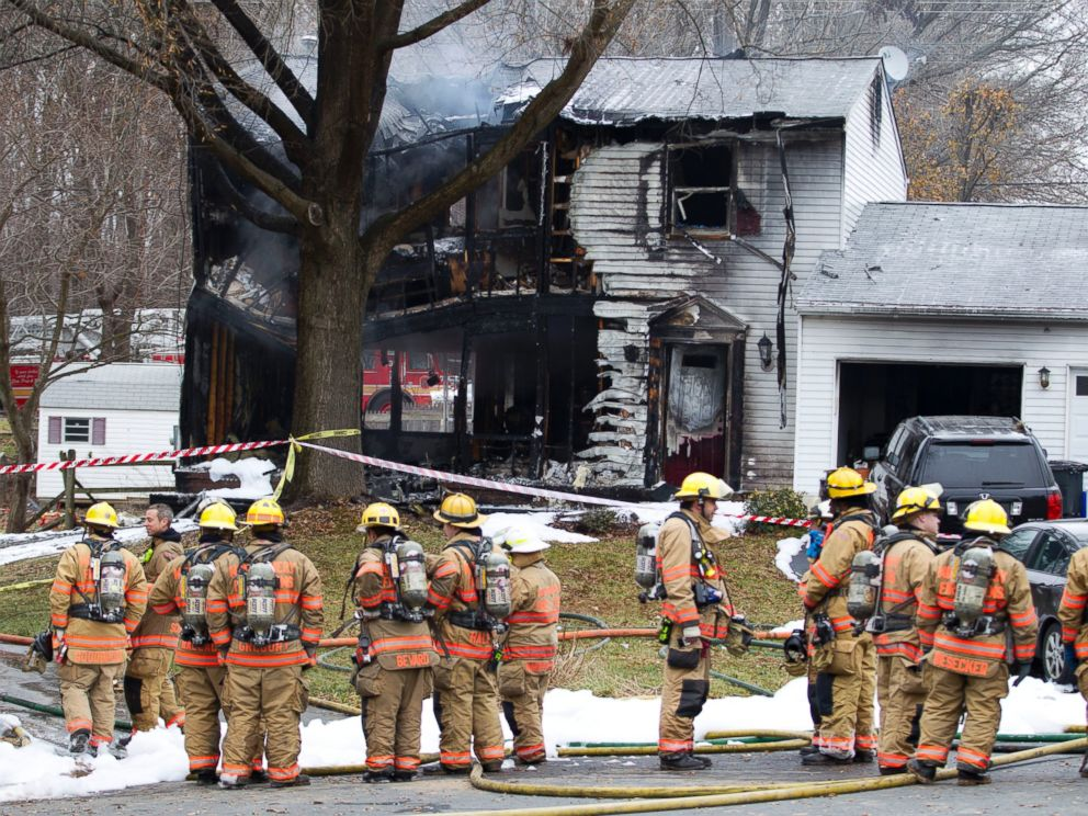 PHOTO: Montgomery County, Md. firefighters stand outside a house where a small plane crashed in Gaithersburg, Md. on Dec. 8, 2014.