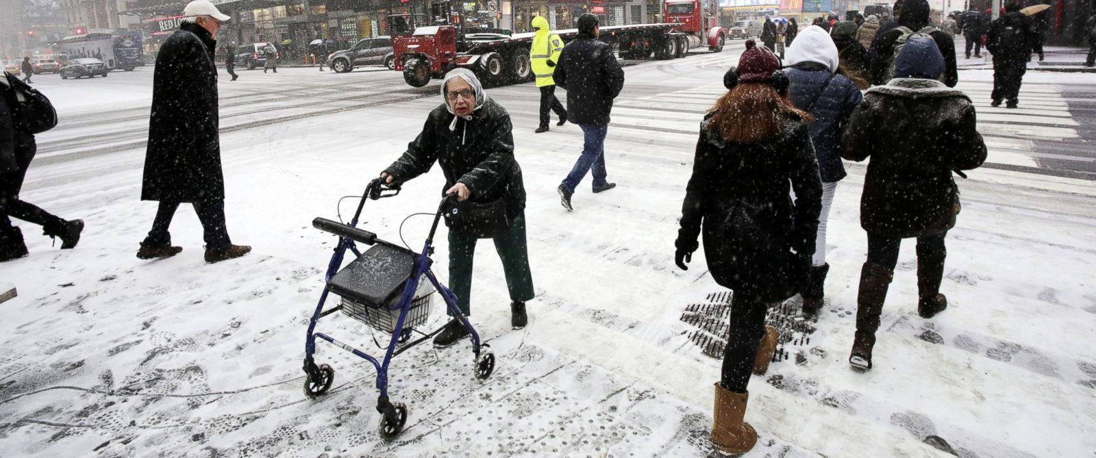 PHOTO: Pedestrians make their way through a snowfall, Jan. 21, 2014 in New Yorks Times Square.