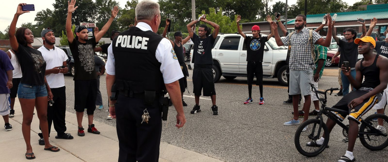 PHOTO: Protestors blocking Florissant Road raise their hands after being approached by police officers who asked them to stop blocking the street in front of the Ferguson police department on Aug. 10, 2014.