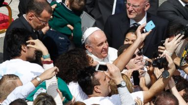 PHOTO: Faithful take pictures with Pope Francis at the end of the Palm Sunday Mass in St. Peters square at the Vatican, Sunday, April 13, 2014.