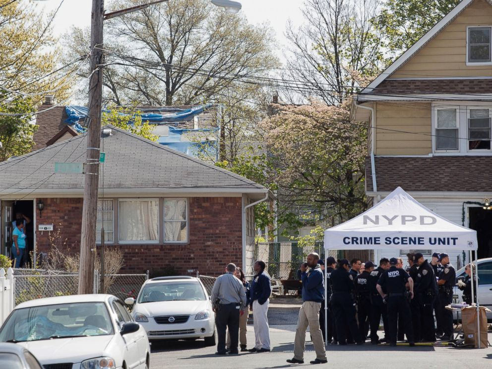 PHOTO: Residents stand in the doorway of their home, left, as they watch police officers investigate the scene of a shooting in the Queens borough of New York, Sunday, May 3, 2015.
