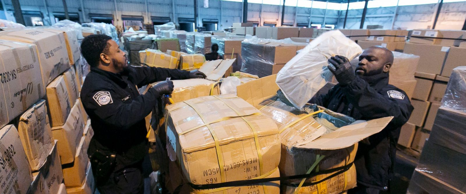 PHOTO: U.S. Customs and Border Protection officers inspect crates of counterfeit bags at a warehouse in Kearney, N.J. Oct. 28, 2015.