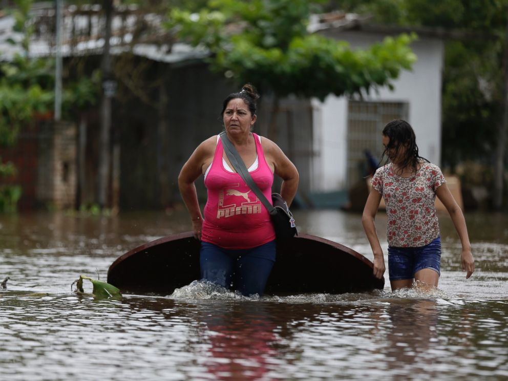 PHOTO:Maria Cristina Olivera and her daughter Catherin carry a table on a flooded street as they leave their home in San Miguel neighborhood in Asuncion, Paraguay, Dec. 27, 2015.